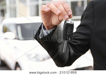 Salesman with key near new car outdoors