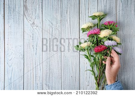 Woman arranging bouquet of chrysanthemum flowers on wooden table
