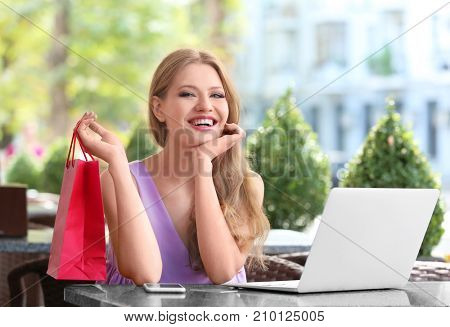 Young woman with laptop and paper bag in cafe
