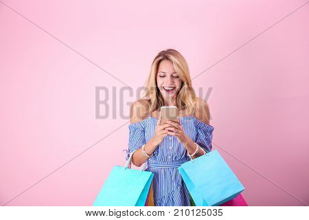 Beautiful woman with paper bags on pink background