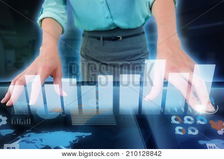 Midsection of businesswoman using digital screen against computer desks in the library