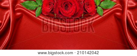 Rose flowers arrangement on red satin background draped with soft folds