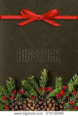Black background with Christmas tree twigs cones berries and red ribbon bow. Flat lay. Top view. Christmas card with copy space for text.