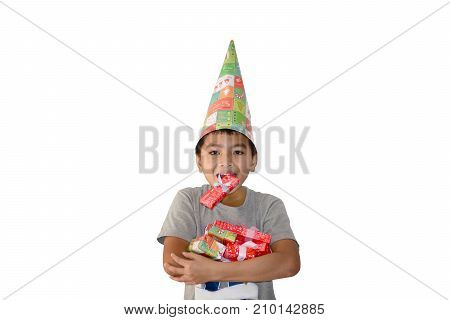 Happy revelation face of asian boy wearing a hand made hat carrying red box in his mouth and holding presents boxes on his chest with white background isolated