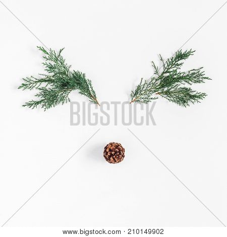Christmas decoration. Christmas deer made of pine branches and pine cone on white background. Flat lay top view square