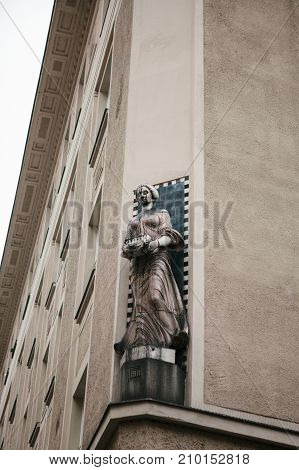 Close-up - historical sculpture - torso of young man in an antique style - decorative element on the facade of building
