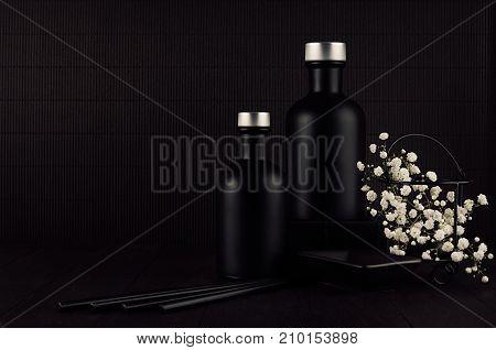 Dark black minimalist interior with blank black bottles white small flowers on dark wood board mock up.