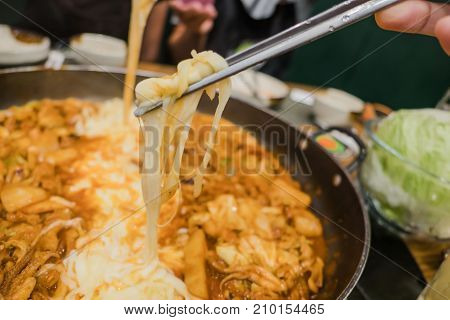 Cheese with chopsticks . Dak Galbi Korean spicy food background .