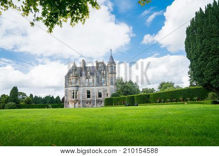 Large green lawn and gardens in front of distant stone castle under blue sky with large white clouds.