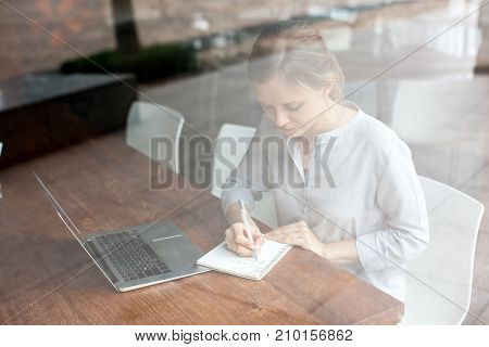 Concentrated student doing homework in cafe. Serious young businesswoman making notes while preparing for meeting. Busy lady working on project. Planning concept