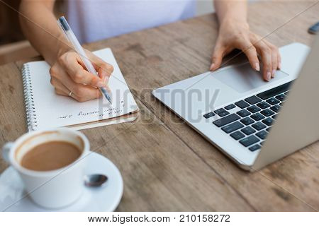 Cropped view of business woman hands working, typing on laptop computer and making notes in notebook at cafe table