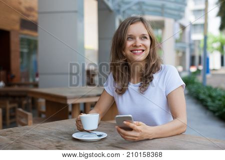 Closeup portrait of smiling young beautiful woman looking away, drinking coffee and using smartphone at cafe table outdoors with street view in background