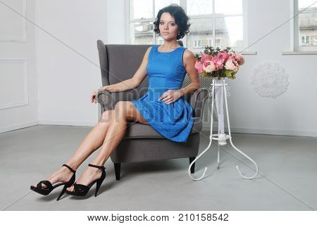 Beautiful young brunette woman with clean skin is sitting in chair in photo studio