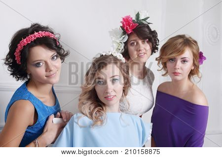 group of four beautiful girls in dresses with flowers in their hair stand in studio focus on girls in blue