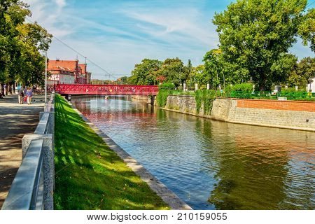 Wroclaw/Poland- August 18, 2017: Cityscape with river Odra, bridge, houses, walking people, green trees and lawns and blue sky