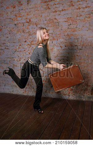 Beautiful smiling woman in striped blouse posing near brick wall in photo studio runs with suitcase late