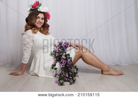 beautiful pregnant woman in white dress and wreath in her hair sits on floor with flowers barefoot in studio
