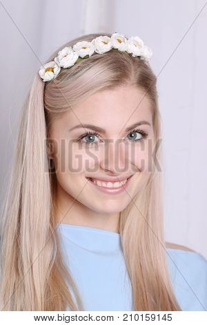 Beautiful smiling young blonde woman with clean skin and flower wreath in her hair on grey background