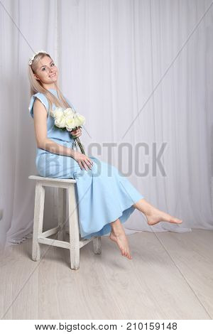 Beautiful young blonde woman with clean skin and flower wreath in her hair sits on stool in photo studio