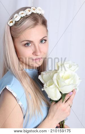 Beautiful young blonde woman with clean skin and flower wreath in her hair on grey background Keep flowers