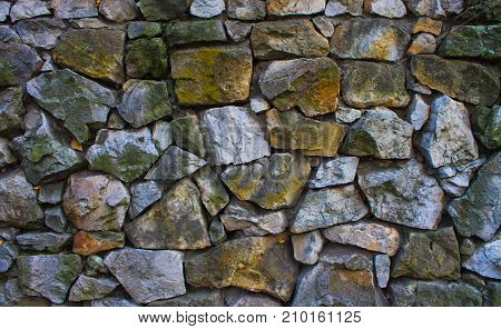 A relief wall made of coarse gray stone.