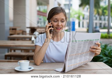 Closeup portrait of worried young beautiful woman talking on smartphone and reading newspaper at cafe table outdoors with street view in background. Front view.