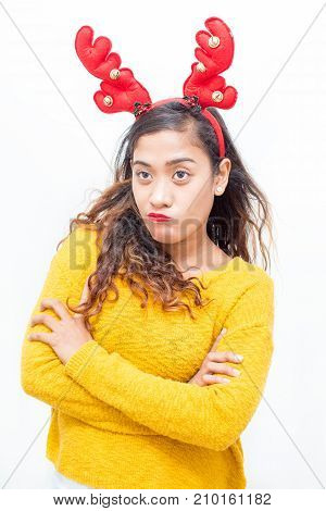 Closeup portrait of angry middle-aged woman wearing toy reindeer horns and standing with her arms crossed. Isolated front view on white background.
