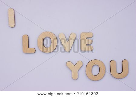 I love you. Words from wooden letters on light grey background. Cute valentine day card