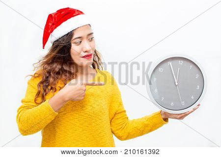 Closeup portrait of content middle-aged woman wearing Santa Claus hat, holding clock and pointing at it. Isolated front view on white background.