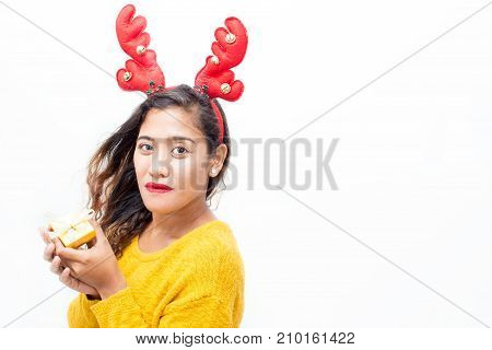 Closeup portrait of content middle-aged woman wearing toy reindeer horns, looking at camera and holding small gift box. Isolated view on white background.