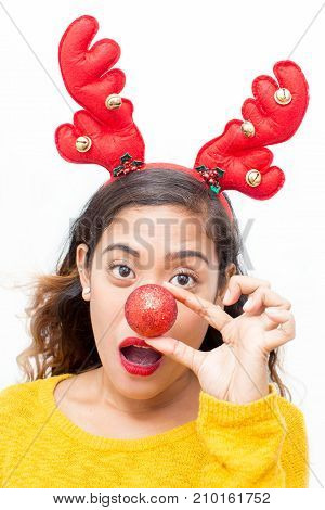 Closeup portrait of playful middle-aged woman wearing toy reindeer horns and holding Christmas ball in front of her nose. Isolated front view on white background.