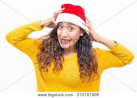 Closeup portrait of stressed middle-aged woman wearing Santa Clause hat, looking at camera and clutching head. Isolated front view on white background.