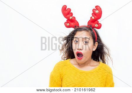 Closeup portrait of surprised middle-aged woman wearing toy reindeer horns and looking at camera. Isolated front view on white background.