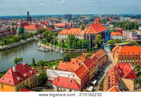 Wroclaw/Poland- August 18, 2017: aerial panoramic cityscape of Tumski Island and bridge, river Odra with touristic boat, historical and modern buildings, summertime, blue sky
