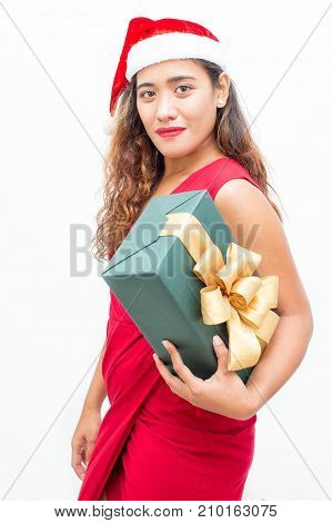 Portrait of confident young Asian woman wearing red dress and Santa hat carrying big gift box. Christmas and shopping concept