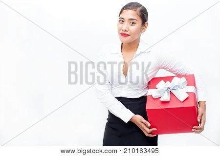 Portrait of happy young Asian businesswoman holding gift box, looking at camera and smiling. Holiday and shopping concept