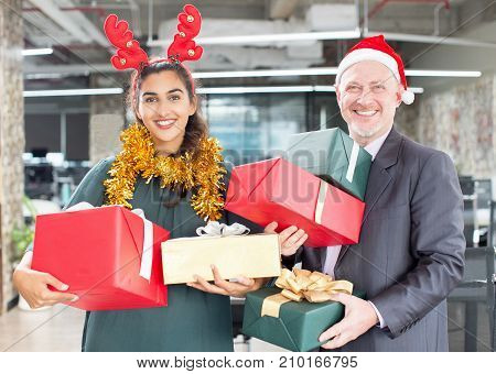 Cheerful employees holding Christmas gifts and looking at camera. Jolly happy boss and female assistant with heap of presents in office. Congratulations concept