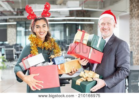 Joyful friendly colleagues enjoying Christmas time in office. Smiling happy business people with heap of Christmas presents looking at camera and ready for gift-giving. Holiday concept