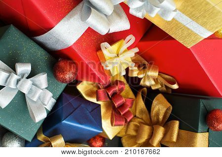 Bright colorful Christmas gifts huddling together. Close-up of packaged presents and Christmas baubles arranging carelessly. New year background concept