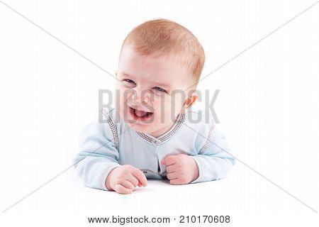 Cute Pretty Little Boy In Blue Shirt Lies On Belly