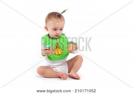 Cute Beauty Little Girl In Green Bib Hold Baby Food