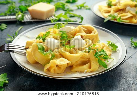 Ravioli with Parmesan and wild rocket on plate.