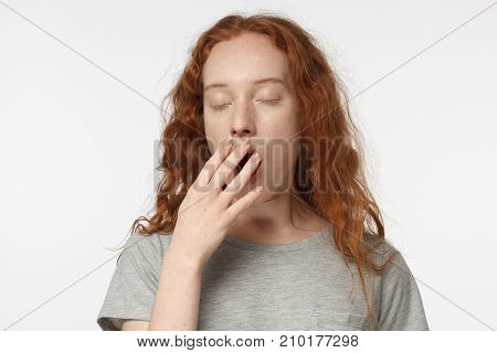 Sleepy Redhead Girl Yawning, Waking Up, Closing Her Mouth With Hand, Isolated On Gray Background