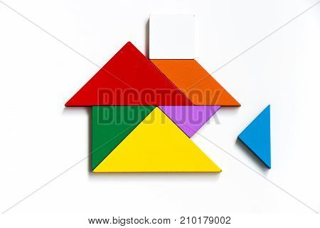 Colorful wood tangram puzzle in home shape wait for fulfill on white background (Concept for build dream house happy family life property investment)