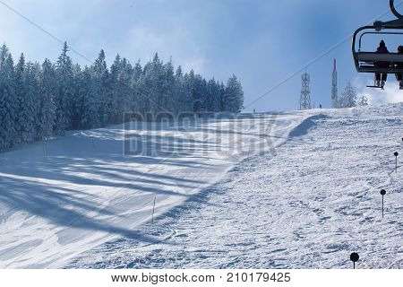 Skiers downhill on ski slopes with trace from skis and snowboards and gondola lift at nice sun day