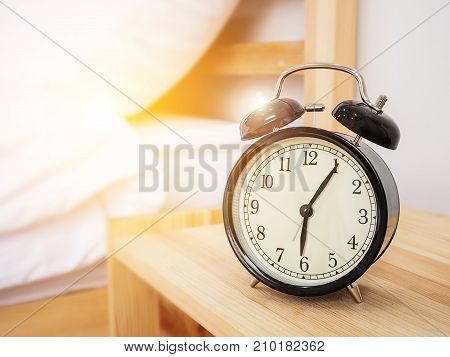 Alarm clock wake-up time concept : Retro alarm clock with five minutes past six o'clock in the morning on wooden bed side table with white bed sheet and morning sunlight background