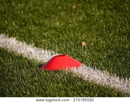 Bright Red Plastic Cone On Painted White Line Of Soccer Field. Plastic Football Green Turf Playgroun