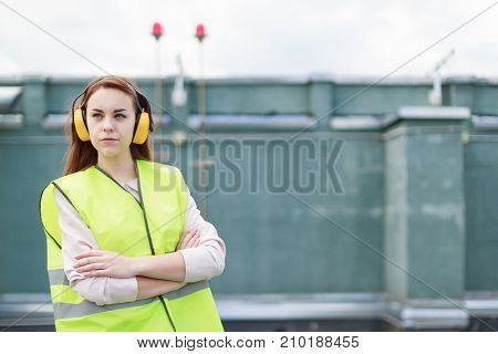 Young Pretty Woman In Green West And Earmuffs Stand On Roof, Hold Tablet