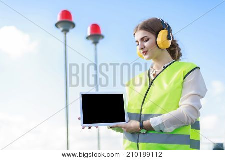 Young Woman In Green West And Earmuffs Stand On Roof, Hold Tablet