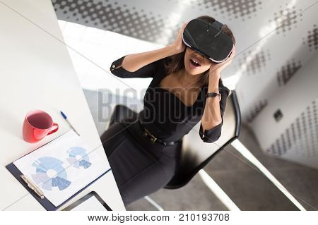 Good Looking Young Business Lady In Black Strong Suite Sit At The Office Table In Vr Glasses